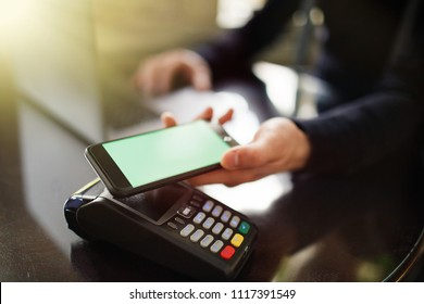 Mobile payments concept with NFC technology or credit card terminal with computer laptop.