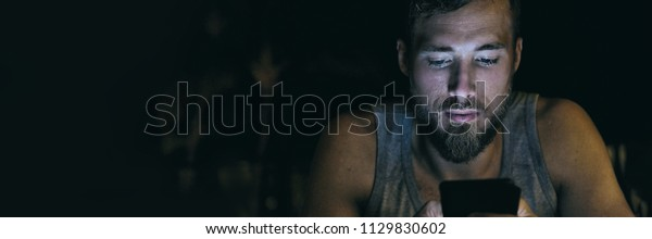 Mobile phone addiction - Young man texting or looking at social media at night - insomnia, online obsession concept. Banner panorama.
