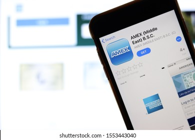Mobile phone with American Express logo on screen close up with website on laptop. Blurred background with AMEX. Los Angeles, California, USA - 27 October 2019, Illustrative Editorial