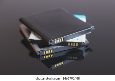 Mobile phone batteries. Battery from a smartphone sitting on top of each other in a black glass mirror table.
