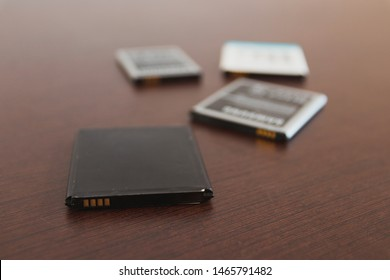 Mobile phone batteries scattered in a wooden table. Each battery is able to provide charge and electrical current to a smartphone.