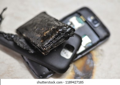 Mobile phone battery explodes and burns due to overheat. Danger, exploded mobile phone battery