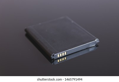 Mobile phone battery with no brand in a dark glass table. This smartphone battery is removable and replaceable.