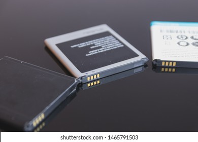 Mobile phone battery side to side in a dark glass table. These smartphone batteries are removable and replaceable.