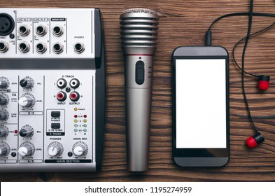 Mobile phone with blank screen, microphone, audio sound mixer and headphones on the table. Audio recording studio concept. Karaoke. Song lyrics.