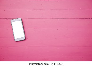 Mobile phone with blank screen mock up on pink wood table background
