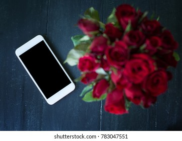 Mobile phone with blank screen and rose red on wooden table background. Happy day celebration with valentine day concept.