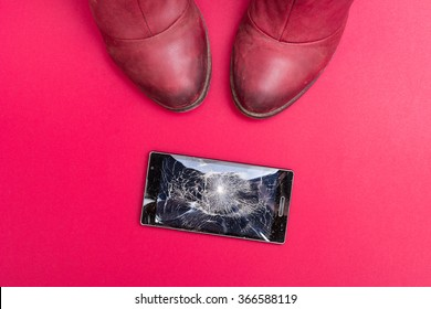 Mobile phone with broken screen on pink floor