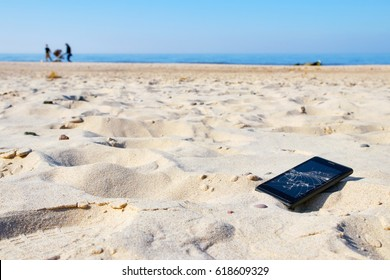 Mobile phone with broken screen in sand on a beach, selective focus.