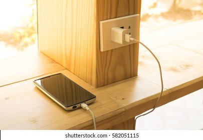 Mobile phone charging plugged on  wooden pole in the coffee shop with sunlight in morning time.