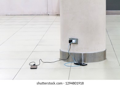 Mobile phone charging plugged in white concrete pole at the Airport, Thailand. Free battery charging station in the airport for traveler. Loading batteries, Charger socket in concrete pole at airport.