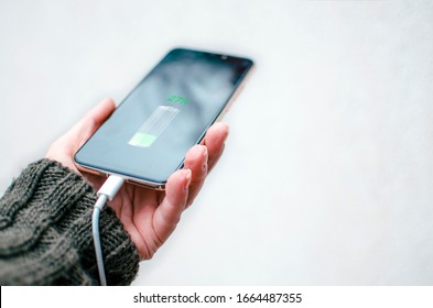 Mobile Phone Charging.Woman hand holding smart phone connecting with electric power for recharge.Copy space
