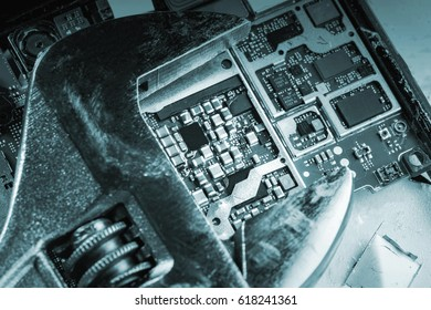 Mobile phone chip with silver wrench, background, close-up. Toned