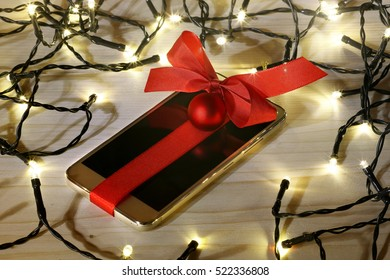 Mobile phone as a christmas gift on wooden desk with led lights
