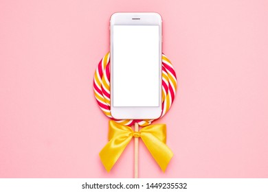 Mobile phone and colorful lolipop with wooden stick, pink, yellow and white spiral on pink background
