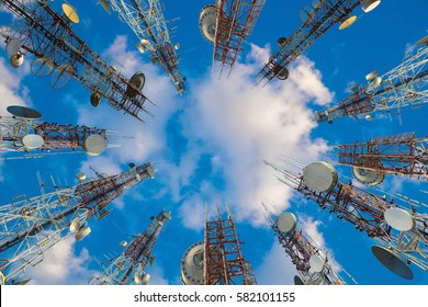 Mobile phone communication antenna tower with cloud on center blue sky, Telecommunication tower perspective.