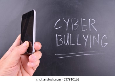 Mobile Phone Concept with blackboard and cyber bullying handwritten