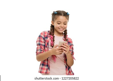 Mobile phone dependence. Girl cute small child smiling to phone screen. She likes internet surfing and social networks. Problem of young generation. Mobile phone and internet addiction or obsession.