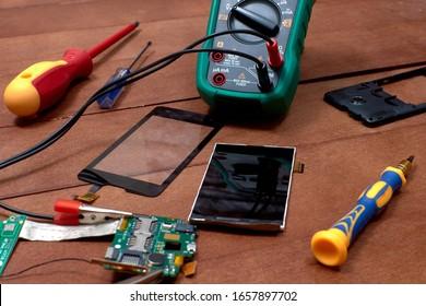 Mobile phone disassembled. Multimeter. Motherboard of the mobile phone. Mobile phone repair shops. The screen and touchpad of the mobile phone. Electronics repair tool.