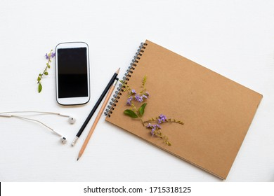 mobile phone and drawing book for  work arrangement flat lay style on background wooden white