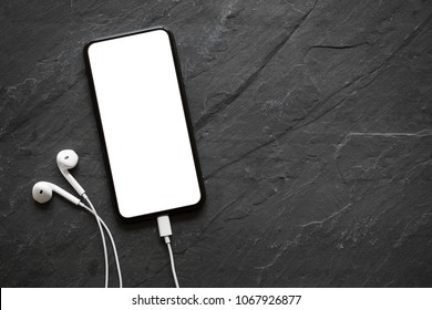 Mobile phone with empty screen and earphones on black stone surface