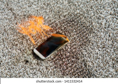 Mobile phone explodes and burns. Cell Phone explosion and fire on a beige carpet. Smart Phone Danger from over use or bad manufacturing. Burning up my phone concept.