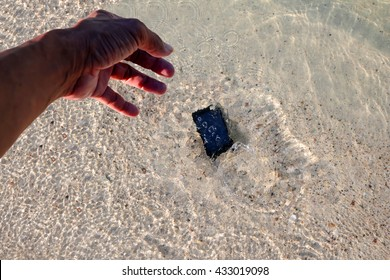 The Mobile phone fall to the sea water near the beach.