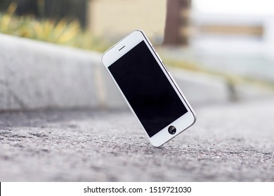 Mobile phone falling and crashes on asphalt, broken smartphone flying down to the ground. Smashed, destroyed, damaged cellphone. Accident with gadget concept. Device needs repairing. Crash test.