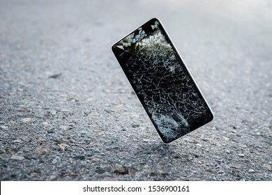 Mobile phone falling and crashes on asphalt, broken smartphone flying down to ground. Smashed, destroyed, damaged cellphone. Accident with gadget concept. Device need repairing. Copy space