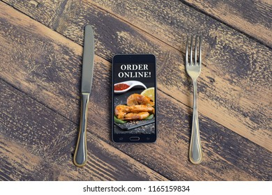 Mobile phone with food order image suggesting to order food online, with fork and knife. Order online concept. Top view with copy space for text. Blogging concept.