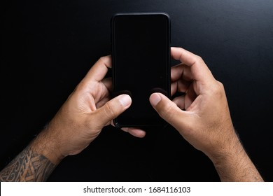 Mobile phone in hand on black background.