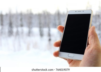 mobile phone in hand on the winter forest background .