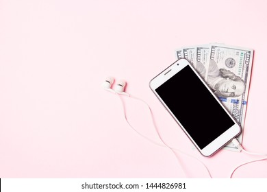 Mobile phone with headphones and money on pink background. Concept of payment and savings