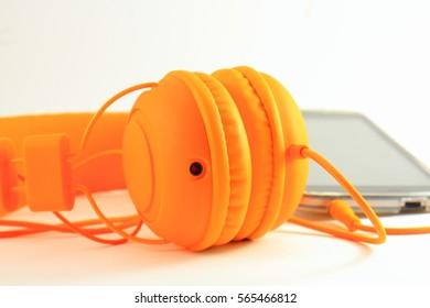 Mobile phone and headphones on orange light background