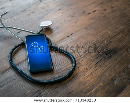Mobile phone with healthcare app on wood table with stethoscope