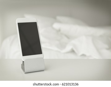 Mobile phone with holder on table in bedroom
