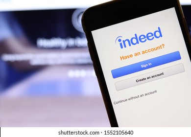 Mobile phone with Indeed logo on screen close up with website on laptop. Blurred background with Indeed Job Search site. Los Angeles, California, USA - 27 October 2019, Illustrative Editorial