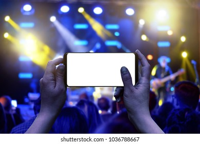 Mobile phone with isolated display in hands. Horizontal position. Live music concert in background. Crowd and lights.