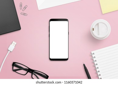 Mobile phone with isolated screen on pink, female desk. Phone with rounde edges mockup. Flat lay.