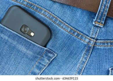 Mobile phone in jeans pocket. Mobile phone camera peeking out of pocket.