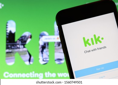 Mobile phone with Kik icon on screen close up with website on laptop. Blurred background with Kik app logo. Los Angeles, California, USA - 9 November 2019, Illustrative Editorial