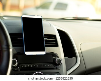 mobile phone located in the center of the vehicle console. Black screen phone in the car
