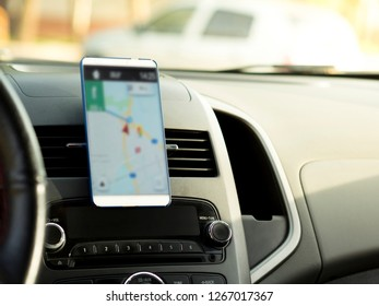 mobile phone located in the center of the vehicle console. Blank screen phone in the car