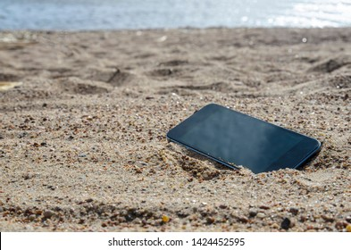 mobile phone lying on the beach in the sand. weatherproof phones, lost phone concept, data loss.