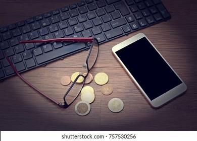 a mobile phone lying on a table with glasses, a keyboard, and small euro coins