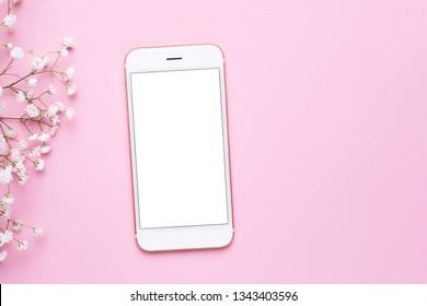 Handy mit Mock-up und weißen Blumen auf rosafarbenem, pastellfarbenem Tisch, Draufsicht in flachem Legestil. Frauenarbeitstisch.Modefarben