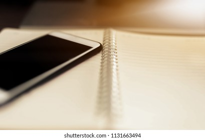 Mobile phone and note book on my desk in the morning.