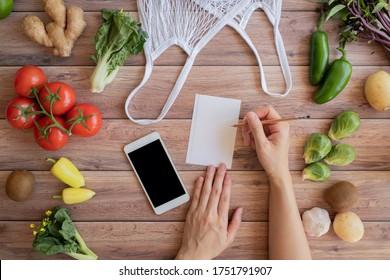 Handy und Notizliste mit dem Netto-Ökosack und frischem Gemüse auf Holzhintergrund. Online-Einkaufs- und Bio-Produkte für Landwirte. Speisen und Kochrezepte oder Ernährungszählung.