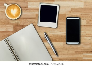 Mobile phone, notebook pen, photo frame and coffee cup on office wooden table with copy space.