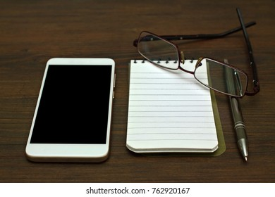 mobile phone with notepad and glasses
